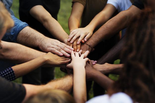 Skupina lidí dávají ruce dohromady